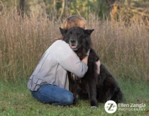 Photo of woman hugging German Shepherd