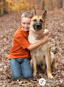 Photo of boy hugging German Shepherd